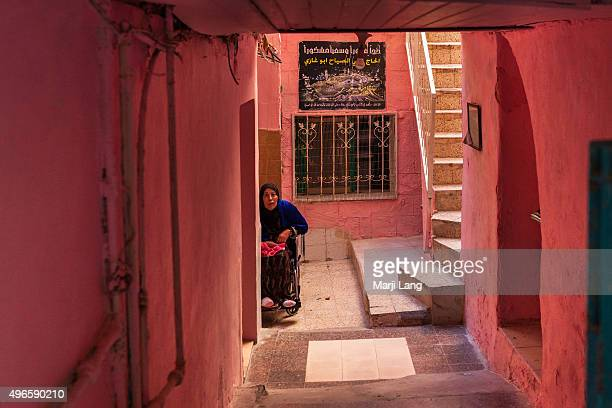 An old woman sitting in her wheelchair at the doorstep of her colorful pink house in the old city of Acre northern Israel