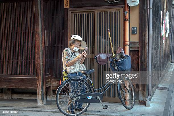 An old woman stops her bike and reads short message on her mobile phone The number of people aged 65 or older in Japan will top a record 329 million...