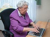 Eine 95-jährige Frau tippt auf einer Laptop-Tastatur, während sie am Schreibtisch sitzt