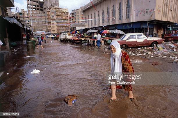 An old woman wades through a war torn flooded street in the Shatilla Palestinian refugee camp after heavy rains