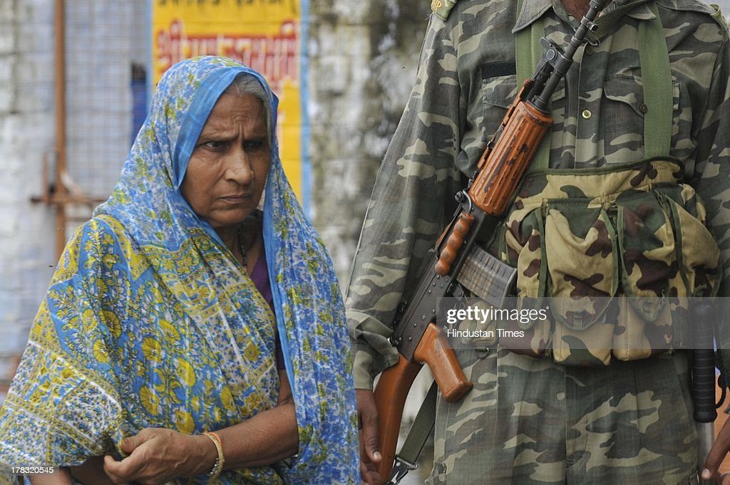 An old woman walks amidst high security on August 28, 2013 in Ayodhya, India. Three days after Vishwa Hindu Parishad (VHP) field Parikarma attempt, Ayodhya saw a heavy presence of security personnel amid Janmashtmi celebrations.