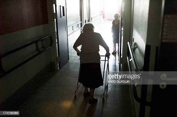 An old woman walks in a corridor at the geriatric hospital of Argenteuil on July 22 2013 as France swelters under a summer heatwave AFP PHOTO / FRED...