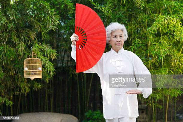 An old woman with a fan in the morning exercise