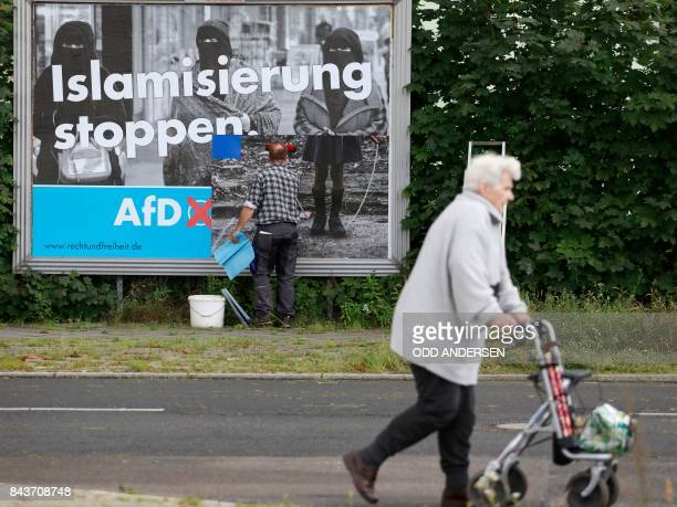 An old woman wlaks with a rollator while a man sticks an Alternative for Germany 's electoral poster reading 'stop islamization' in Berlin on...