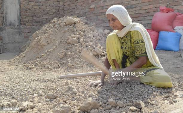 An old women is busy in her daily work as the world celebrates women day all over the world