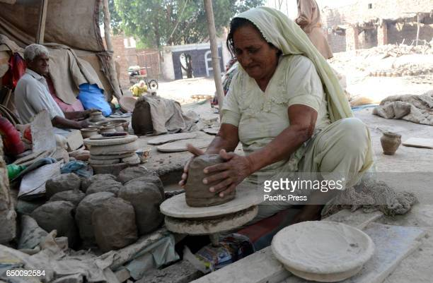 An old women is busy in making mud item on her work place as the world celebrates International Women day and this simple women is not awareness from...