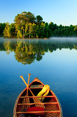 An old wooden canoe on calm lake