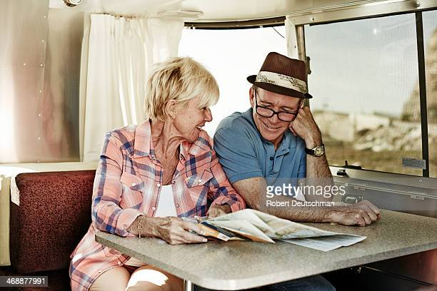 An older couple looking at a map inside a camper.