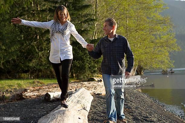 An older couple walking near a lake.