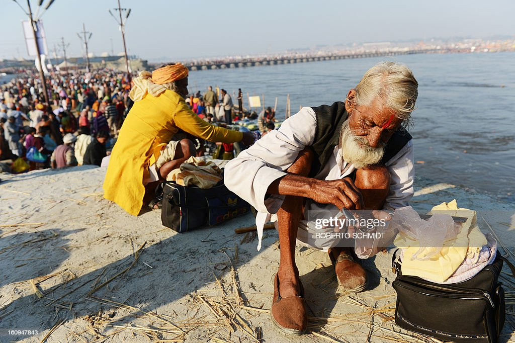 An older Indian Hindu devotee gets ready to mark his forehead after bathing in the confluence of the Yomuna and Ganges river during the Maha Kumbh festival in Allahabad on February 8, 2013. The Kumbh Mela in the town of Allahabad will see up to 100 million worshippers gather over 55 days to take a ritual bath in the holy waters, believed to cleanse sins and bestow blessings.
