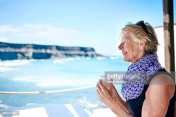 An older lady smiles holding coffee cup by beach