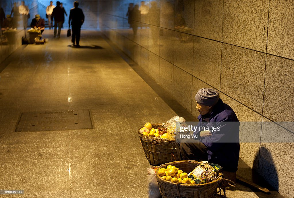 An older man waits to sale his fruits at an underground passage on November 6, 2012 in Chongqing, China.