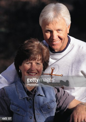 an older man wearing a white shirt sits behind an older woman wearing a purple shirt and denim jacket as they smile : Stock Photo
