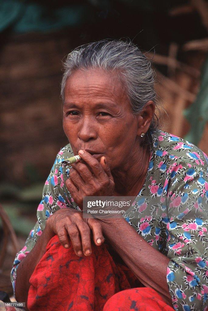 BURMA YANGON RANGOON MYANMAR An older woman a market vendor takes a break to smoke a Burmese cigarette which is like a cheroot or cigar