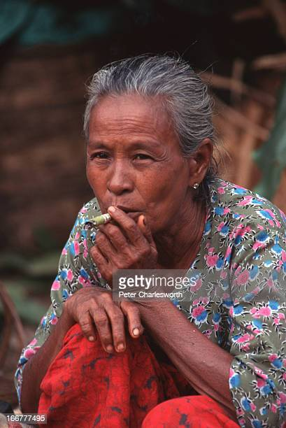 BURMA YANGON RANGOON MYANMAR An older woman a market vendor takes a break to smoke a Burmese cigarette which is like a cheroot or cigar