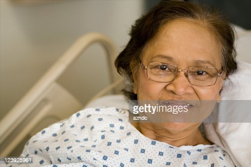 An older woman in a hospital gown laying on a bed