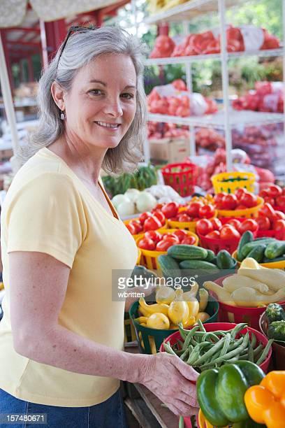 An older woman shopping for fresh vegetables