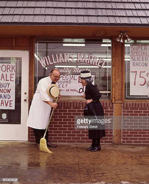 An old-fashioned butcher greets an elderly customer outside his store