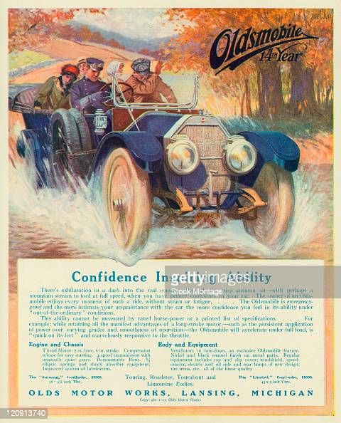An Oldsmobile automobile is shown in a magazine from 1911 The car with a driver and four passengers is dashing down a country road and crossing a...