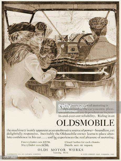 An Oldsmobile car interior is pictured in a magazine advertisement from 1909 The car which is on a country road has two women and a man seated inside...