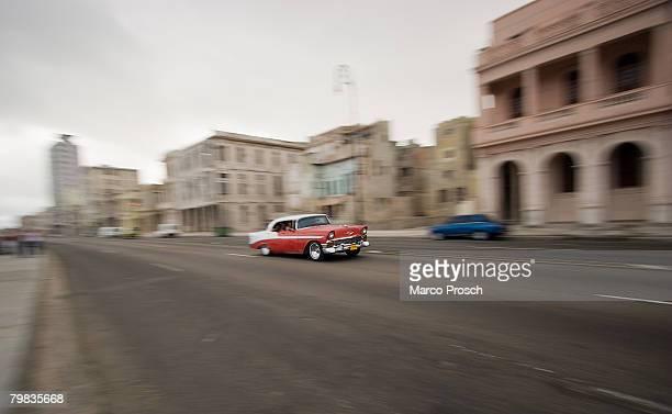 An oldtimer drives on the seven kilometre sea wall 'Malecon' on February 26 2006 in Havana Bay Cuba