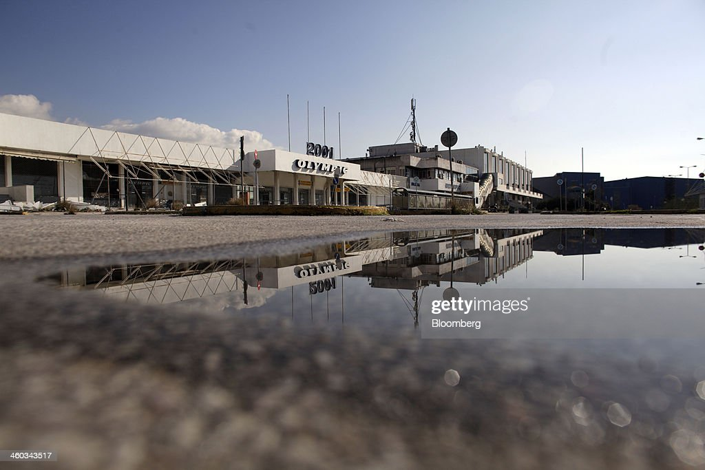 An Olympic 2001 logo at the entrance to the west terminal is reflected in a puddle at the former Athens International Airport in the Hellenikon district of Athens, Greece, on Friday, Dec. 3, 2014. Hellenikon is the largest of Greece's land development projects, three times the size of the Principality of Monaco. Photographer: Kostas Tsironis/Bloomberg via Getty Images