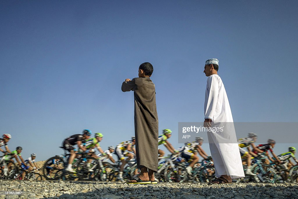 An Omani biy watches the pack riding during the third stage of the Tour of Oman, from Nakhal Fort to Wadi Dayqah Dam, on February 13, 2013, in Oman. The six-stage race, which follows the Tour of Qatar, won by Britain's Mark Cavendish last week, culminates on February 16 at Matra Corniche.