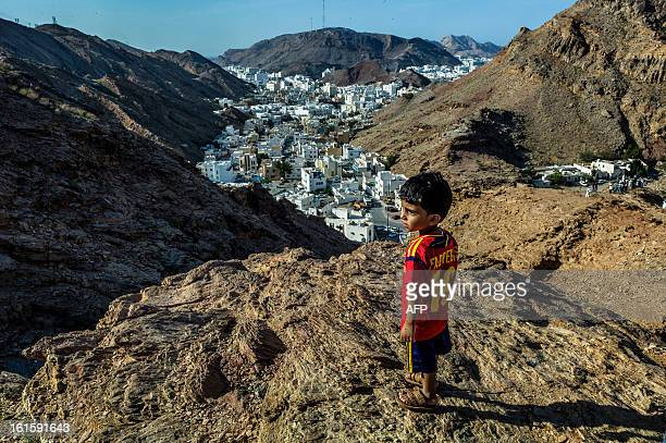 An Omani child waits to watch the pack riding during the second stage of the Tour of Oman from Fanja in Bidbid to Al Bustan on February 12 in Oman...