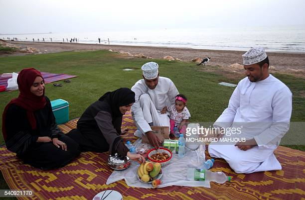 TOPSHOT An Omani family gathers to break its fast at the beach in the capital Muscat on June 17 2016 during the Muslim holy month of Ramadan / AFP /...
