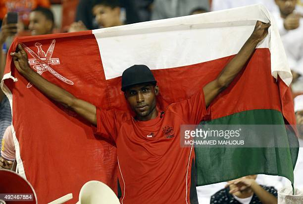 An Omani fan holds his national flag as he cheers on his team during the AFC qualifying football match for the 2018 FIFA World Cup between Oman and...
