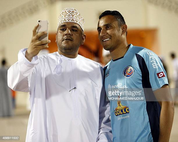 An Omani fan takes a picture of himself with Costa Rica and Real Madrid goalkeeper Keylor Navas during a training session in Sohar northwest of...