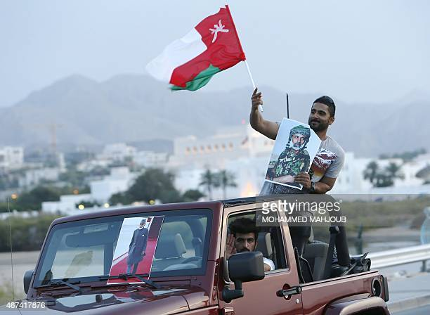 An Omani man holds his national flag and a portrait of Omani leader Sultan Qaboos bin Said who flew home the previous day after he spent more than...