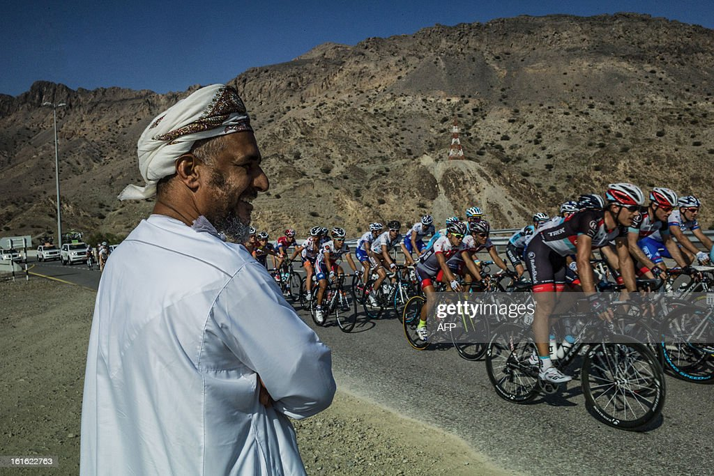 An Omani man watches cyclists compete during the third stage of the Tour of Oman, from Nakhal Fort to Wadi Dayqah Dam, on February 13, 2013, in Oman. The six-stage race, which follows the Tour of Qatar, won by Britain's Mark Cavendish last week, culminates on February 16, along Matra Corniche.