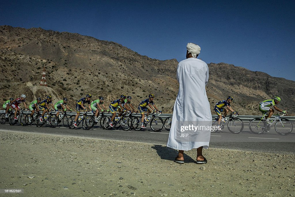 An Omani man watches cyclists competing during the third stage of the Tour of Oman, from Nakhal Fort to Wadi Dayqah Dam, on February 13, 2013, in Oman. The six-stage race, which follows the Tour of Qatar, won by Britain's Mark Cavendish last week, culminates on February 16, along Matra Corniche.