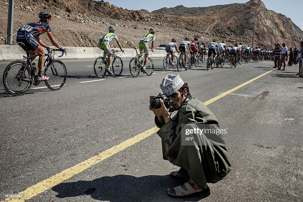 An Omani person takes pictures of the pack riding during the third stage of the Tour of Oman, from Nakhal Fort to Wadi Dayqah Dam, on February 13, 2013, in Oman. The six-stage race, which follows the Tour of Qatar, won by Britain's Mark Cavendish last week, culminates on February 16 along the Matra Corniche.