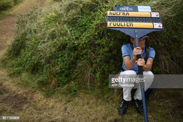 An oncourse scoreboard carrier accompanying the the group containing US golfer Brooks Koepka and England's Ian Poulter shelters from the rain under...