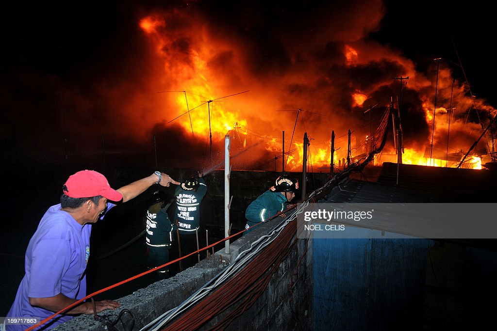 An onlooker reacts as firefighters attempt to extinguish a fire that engulfed a residential area in Manila on January 19, 2013. Almost 50 houses were destroyed leaving a hundred families homeless, according to local media reports.