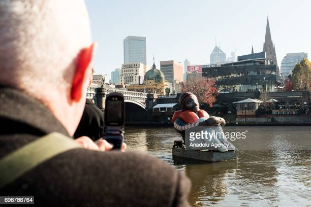 An onlooker takes a photo of the travelling artwork titled 'Inflatable Refugee' on the Yarra River on June 17 2017 in Melbourne Australia The five...