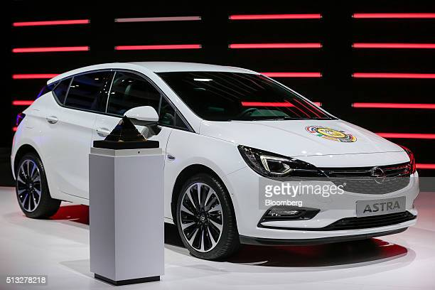 An Opel Astra automobile produced by General Motors Co sits on display with the car of the year trophy on the second day of the 86th Geneva...