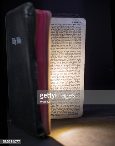 An open bible with the passages illuminated. Black background : Stock Photo