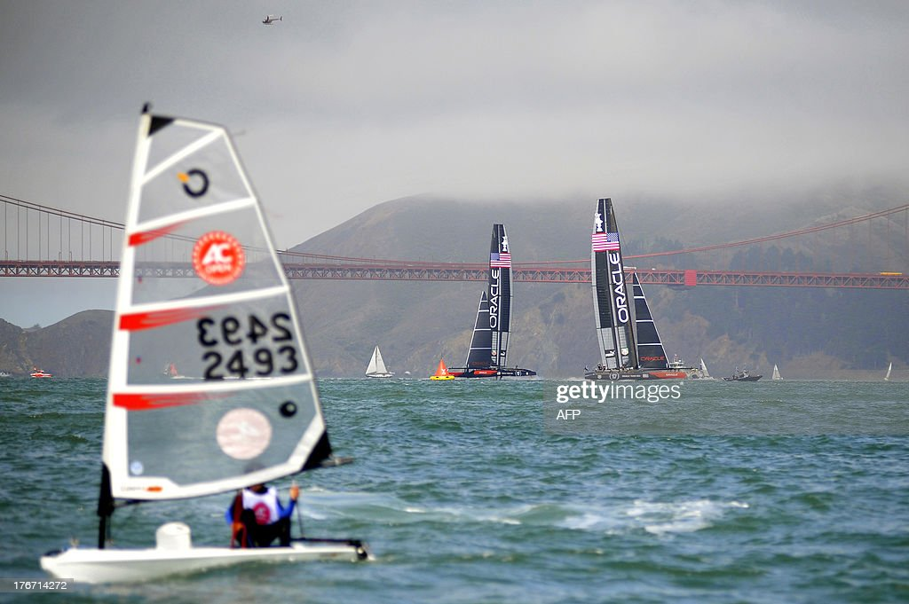 An OPen BIC youth sailor is seen in the foreground as Oracle Team USA sails their AC-72 racing Yachts near the Golden Gate Bridge during a practice session in San Francisco, California. on August 17, 2013. AFP PHOTO/Josh Edelson