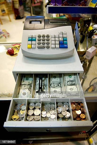 An open cash drawer showing bills and coins