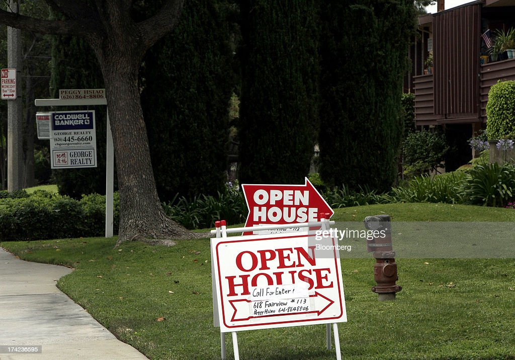 An 'open house' and 'for sale' signs stand outside a townhouse complex in Arcadia, California, U.S., on Sunday, July 21, 2013. Sales of previously owned houses unexpectedly dropped in June, hurt by a lack of supply and rising mortgage rates that may slow the rebound in the U.S. real-estate market. Photographer: Jonathan Alcorn/Bloomberg via Getty Images
