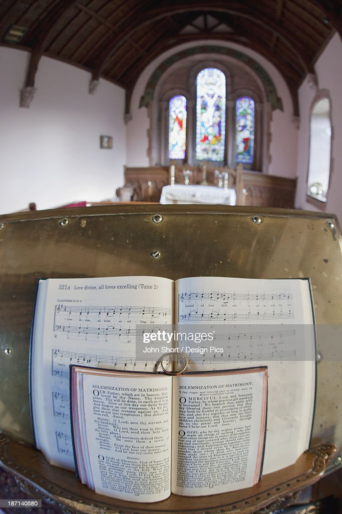 An Open Hymnal And Bible On A Podium Inside A Church