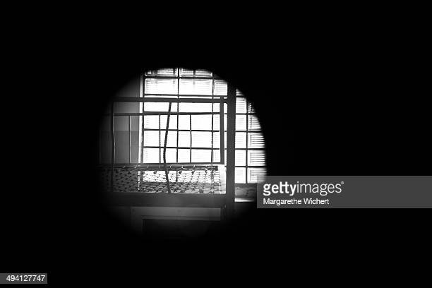 An open peephole allows a peak inside into a detention cell with a bed without mattress at the former prison of the East German Ministry of State...
