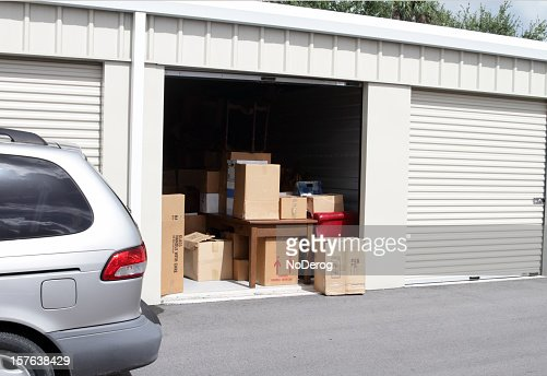An open self storage unit with a van parked next to it