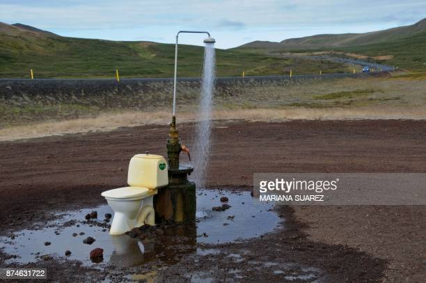 TOPSHOT An openair toilet and a hot spring shower are seen in the middle of nowhere on the road to the Krafla geothermal power station and lava...