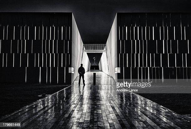 CONTENT] An openair tunnel frames the silhouette of a man and the distant Australian Parliament House Canberra