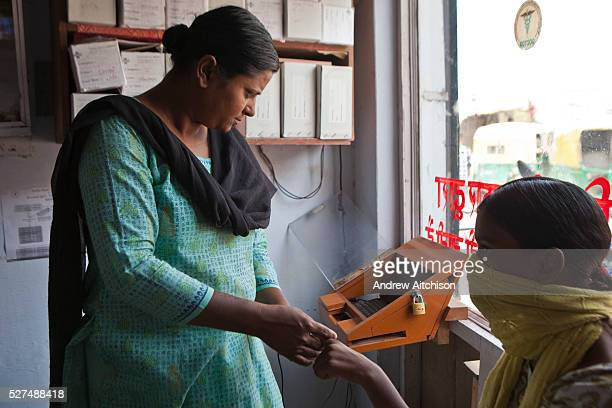 An Operation Asha female worker uses the fingerprint scanner to access the biometric patient record computer system at a health clinic in Meethapur...