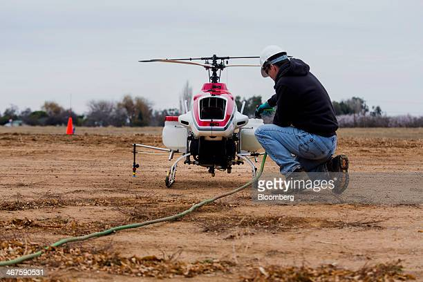 An operator adds water to sprayer containers on a Yamaha RMax Unmanned Aerial Vehicle before a crop dusting test flight at a University of California...